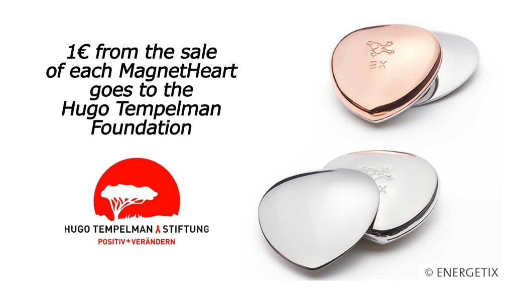 One Euro from the sale of each heart goes to the Hugo Tempelman Foundation, with charity logo below of red sun and tree silhouette, next to two Magnet Hearts - one stainless steel and one with copper