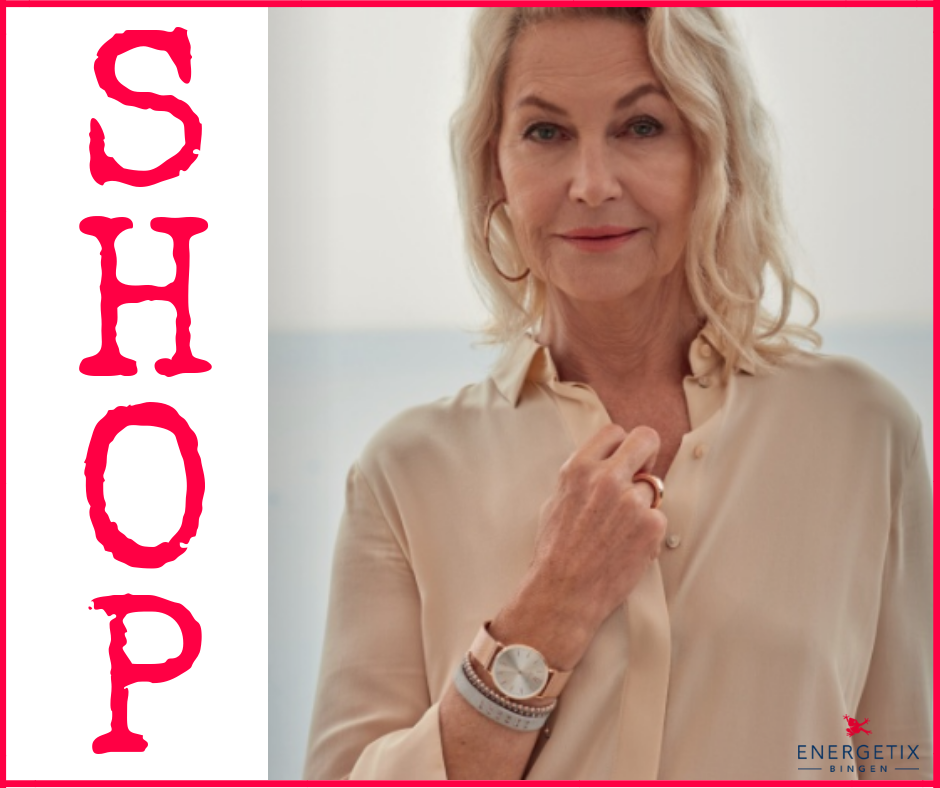 Large letters saying SHOP to link to webshop. Head and shoulders photo of mature woman in front of sea, holding shirt lapel, wearing rose-gold magnetic watch and magnet bracelets, with matching magnet ring and magnet hoop earrings