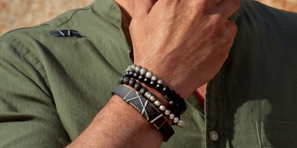 Mans wrist wearing two magnetic bracelets, one with mixed beads and one black silicon with abstract metal design centre piece