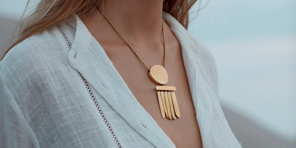 Woman wearing gold-plated magnetic pendant on gold-plated chain - large brushed gold-plated circle with hanging vertical bar, and 5 dangling bars hanging below