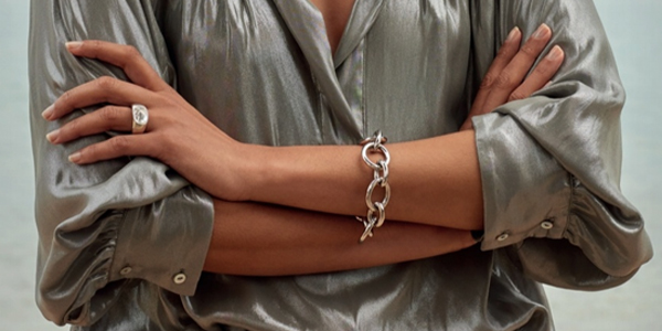 Woman with arms crossed wearing a steel magnetic bracelet of large round links, and steel magnetic ring with large crystal