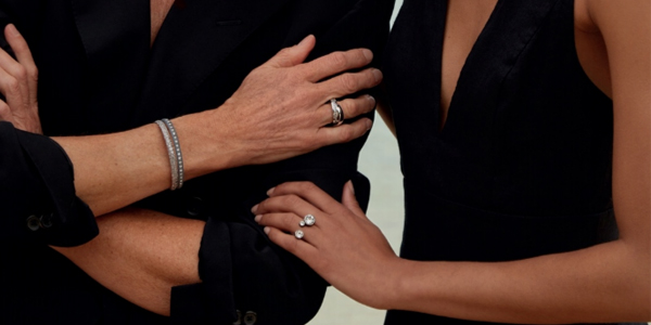 Woman with arms crossed, wearing elegant magnetic jewellery, with another lady standing next to her holding her arm, wearing a stylish double crystal magnetic ring