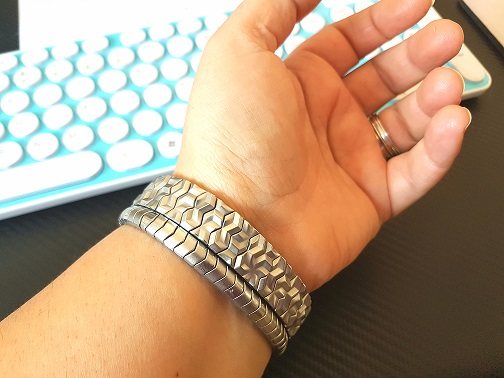 photo of a wrist wearing two stainless steel magnetic bracelets, next to a retro computer keyboard