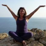 Photo of Barbara T sitting cross legged on the rocks by the sea with her hands up in the air, smiling
