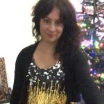 Photo of Karen G, wearing a sparkly sequined top, with her long dark hair pulled to one side