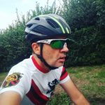 side photo of Simon G riding a bicycle, wearing a helmet and wraparound sunglasses