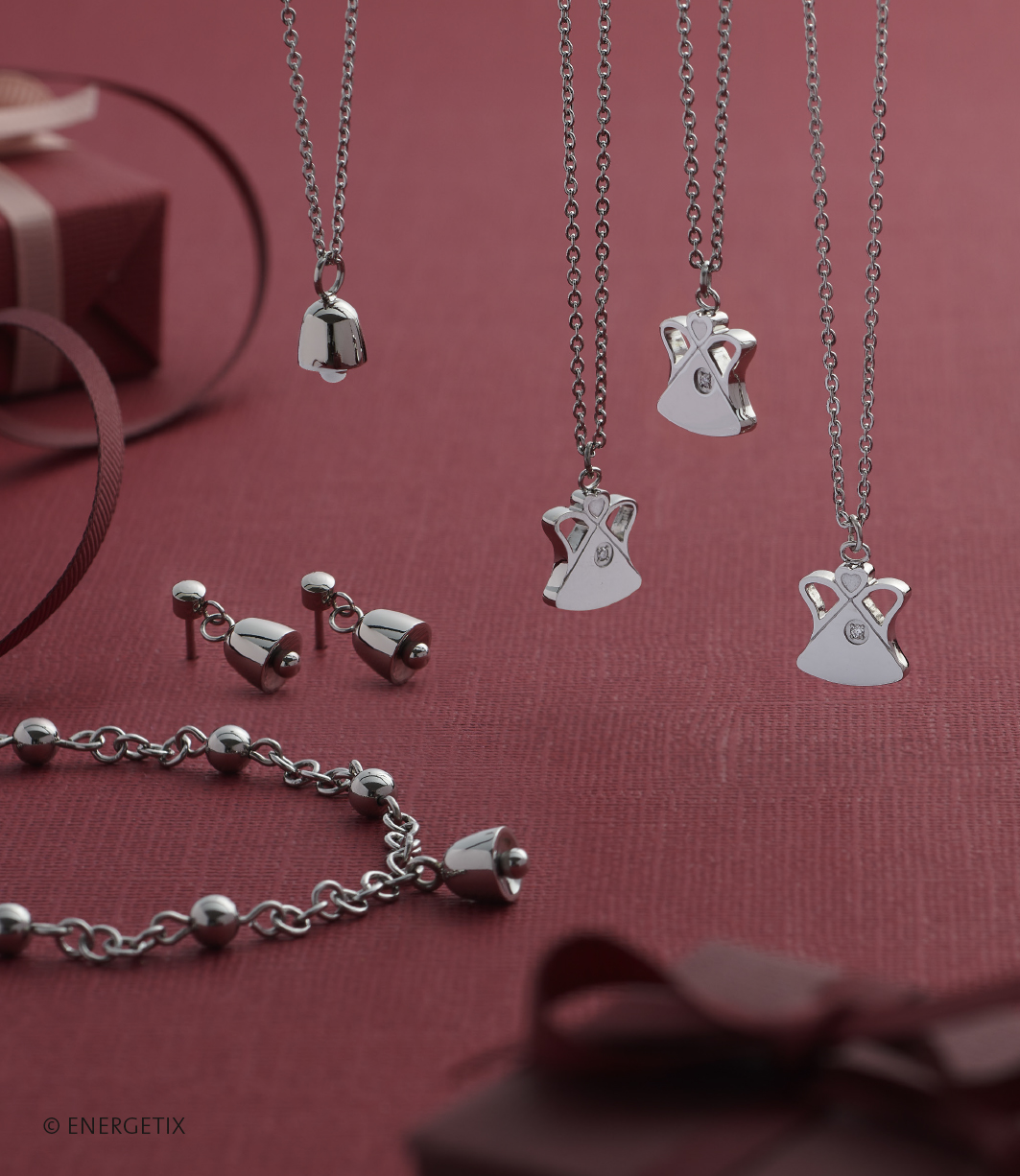 Stainless steel magnetic bracelet with bell shaped charm, next two two bell shaped ear droppers in matching steel colour. Above which hangs a bell shaped pendant on silver colour chain, and three angel pendants with a small diamond over their heart, hanging on chains