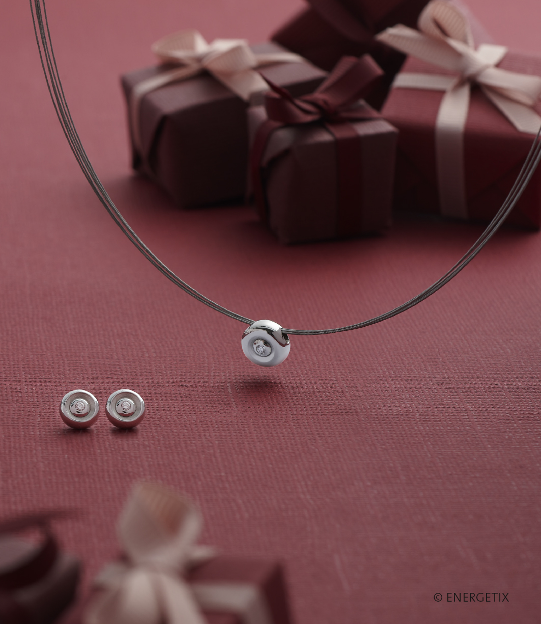 Round, stainless steel ear studs with certified diamond centres, next to a round stainless steel pendant with diamond centre, handing from a steel necklace. These are on a burgundy table cloth with small gift boxes in the background