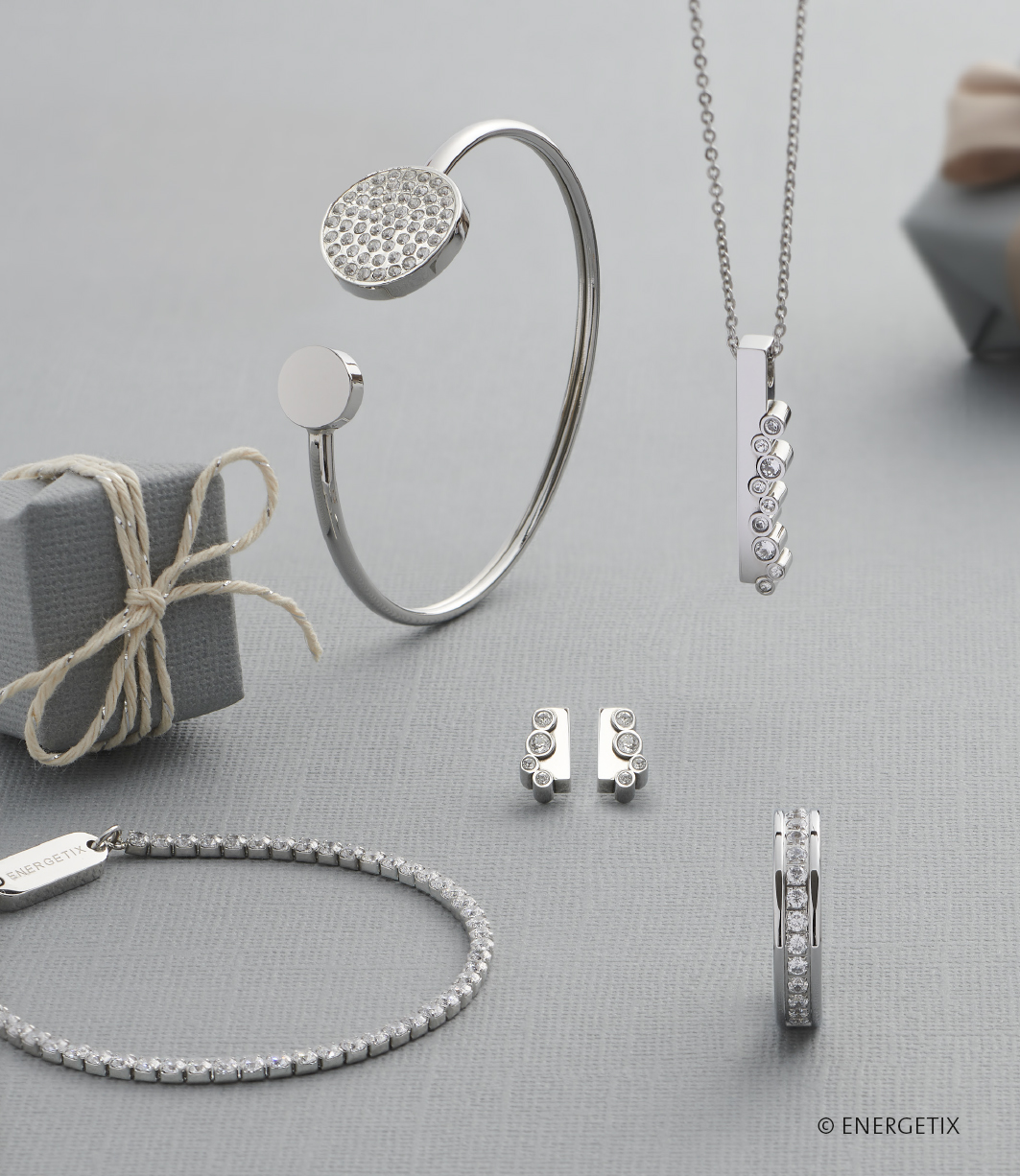 Selection of stainless steel magnetic jewellery on silver tablecloth. The magnetic bangle has two discs of varying sizes, one encrusted with crystals. A pendant adorned with crystals hangs from a chain, over matching ear studs. A magnetic bracelet with crystal links lays on the table next to a steel ring lined in the centre with crystals.