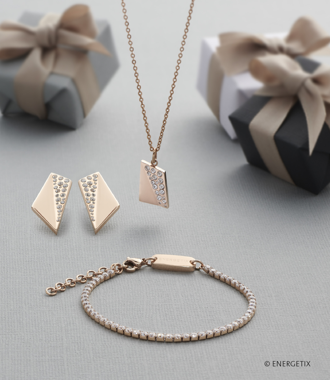 Large gold quadrilateral ear studs with triangle section encrusted with crystals, next to hanging pendant of matching design. Laying on the grey tablecloth in front is a magnetic bracelet of crystal links. Small gift boxes are scattered in the background