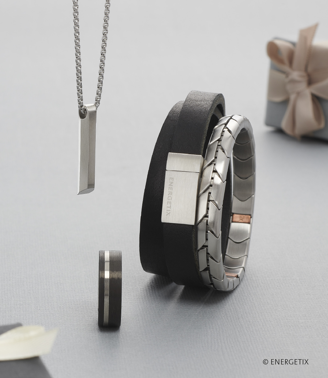 Stainless steel polished pendant hanging from a chain above a steel mens rings with carbon black finish. A double wrap leather magnetic bracelet with steel fastener, next to a stainless steel magnetic flexi bracelet with chevron style design