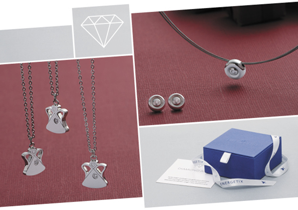 Three Angel magnetic pendants hanging on necklaces, next to diamond ear studs and diamond solitaire pendant on necklace, above a blue gift box with silver ribbon
