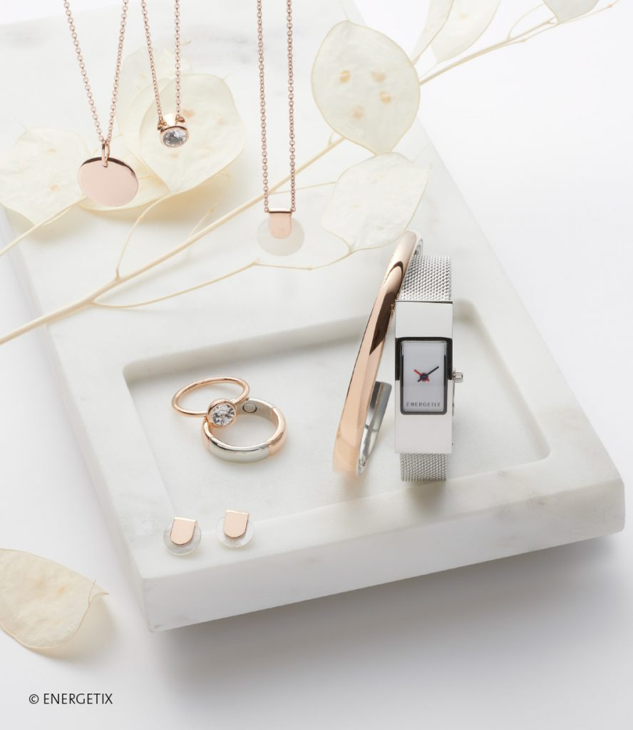 Collection of hanging pendants on chains, in rose gold and mother of pearl. Two rings in rose gold, one with large Swarovski crystal. Rose gold bangle next to steel watch, with delicate rose-gold and mother-of-pearl ear studs