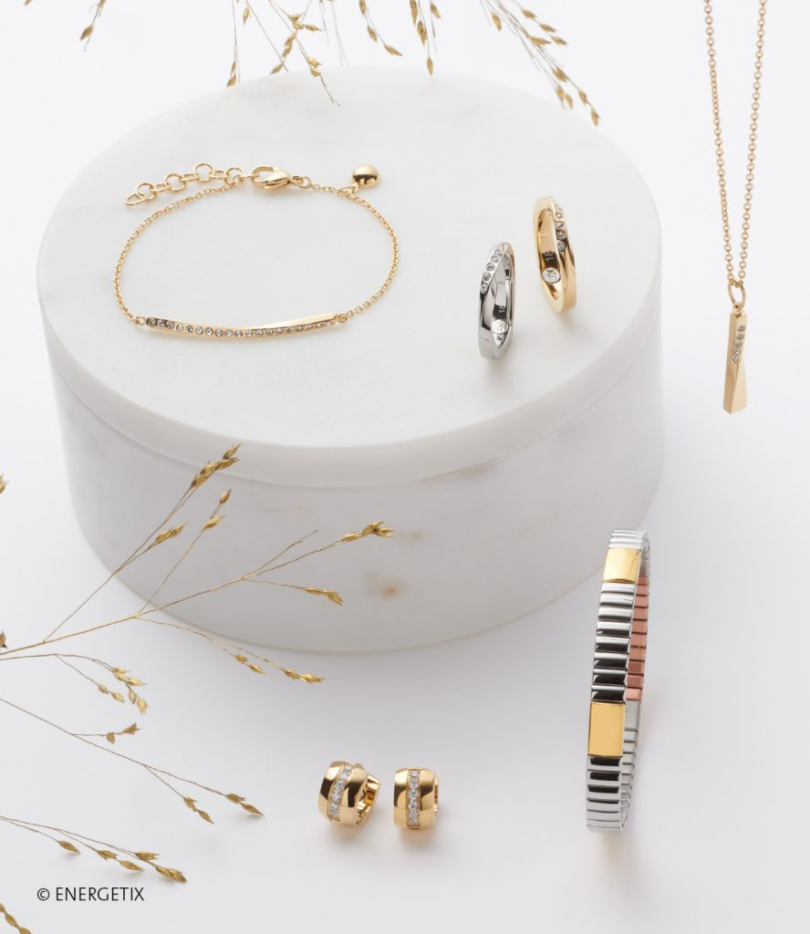 Delicate gold magnetic bracelet with twisted bar adorned with Swarovski crystals, next to two matching rings, one stainless steel and one gold. A gold coloured pendant with Swarovski crystals hangs from a gold chain necklace. Below are gold creole ear studs with a centre row of crystals, next to a steel and gold flexible magnetic bracelet