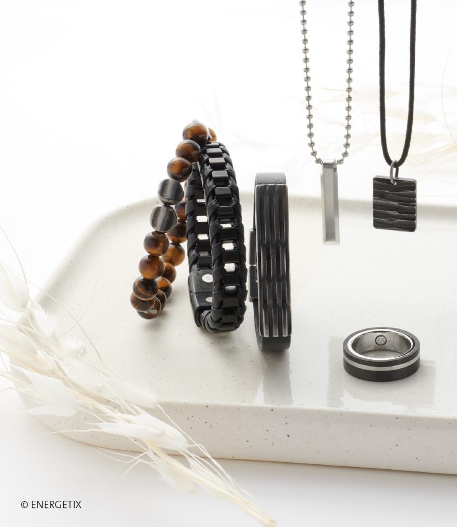 Row of magnetic bracelets - tigers eye beads, braided leather and black steel, and black leather with black steel centre element. Two pendants hand from chains, with a black and steel coloured ring below.