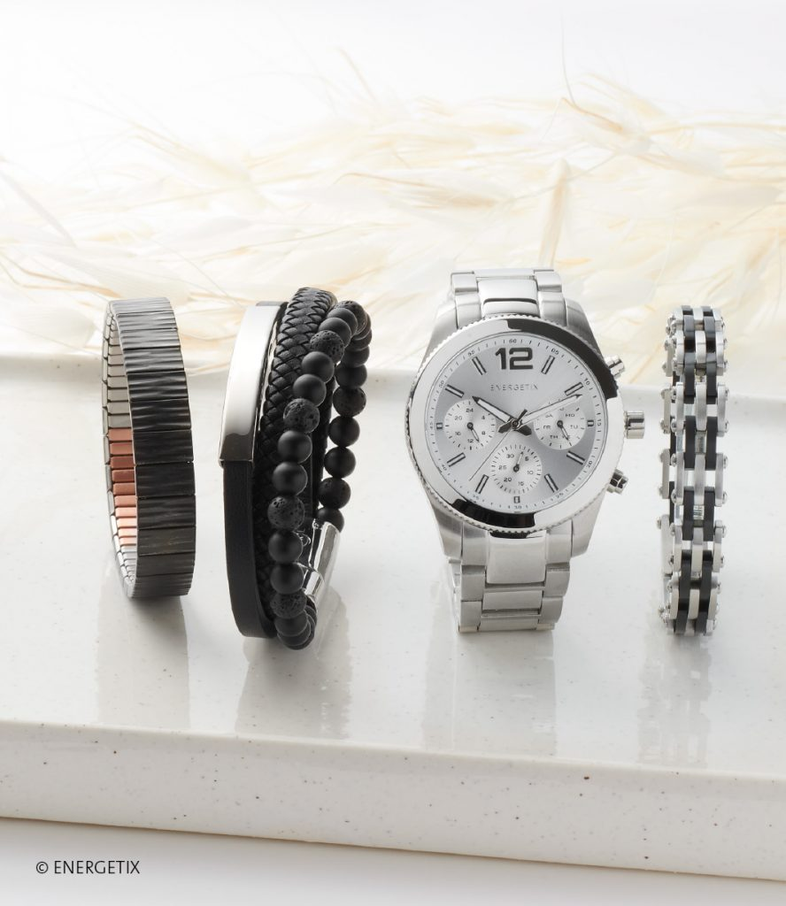 Flexible magnetic bracelet in brushed black colour, next to three-in-one bracelet of black leather, stainless steel and black gem stones. A large stainless steel watch sits between these and a bike chain styled bracelet